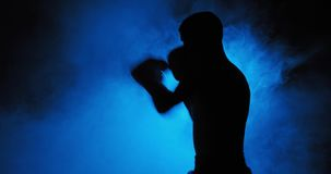 Boxing. Muscular young man in boxing gloves shows the different movements and strikes in the studio on a dark background. Fog in the background stock footage