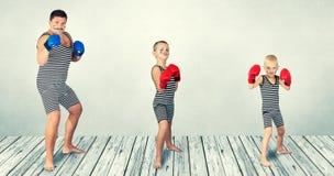 boxing Pai e dois filhos em trajes do vintage para jogar pugilistas Família de encaixotamento fotografia de stock royalty free