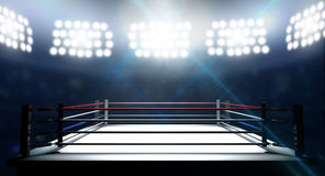 Boxing Ring In Arena. An boxing ring surrounded by ropes spotlit by floodlights in an arena setting at night Stock Photo