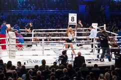 Boxing ring girls holding a board with round number Stock Photography