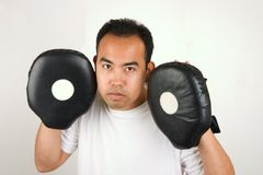Boxing Trainer 1. Boxing trainer holding focus mitts Royalty Free Stock Photography