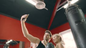 Boxing trainer doing selfie photo with woman boxer on punching bag background. stock video footage