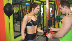 Boxing trainer man helps to dress up boxing gloves to young woman in fitness club stock video