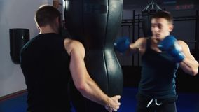Boxing training. man boxing, it helps partner on training stock footage