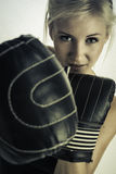 Boxing woman. Determined woman with boxinggloves ready to punch royalty free stock photography