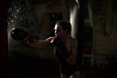Boxing woman in black body hitting punching bag. Royalty Free Stock Photography