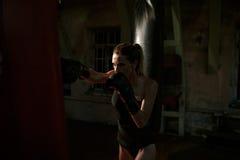Boxing woman in black body hitting punching bag. Stock Photo