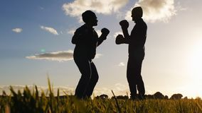 Boxing workout with trainer outdoors. Low angle shot of opponents` silhouettes in boxing gloves sparring on sunset sky. Background. Fighter with glasses stock video footage