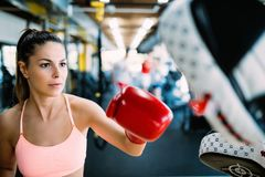Boxing workout woman in fitness class ring. Man trainer holding sport mitts in gym royalty free stock images