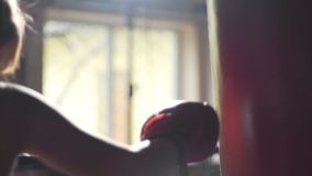 Boxning för kvinnlig idrottsman nen i idrottshall och att anfalla stansa påsen som förbereder sig för konkurrens stock video