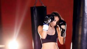Boxning för ung kvinna med att stansa påsar långsam rörelse lager videofilmer