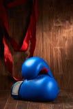 Boxningbakgrund med handskar och rött förbinder mot träbakgrund fotografering för bildbyråer