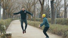 Boxninggenomkörare med instruktören utomhus Lagledaren med den gula toppluvan och unga caucasian mannen i svart hoodie som värmer stock video