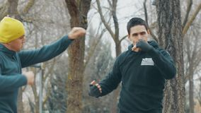 Boxninggenomkörare med instruktören utomhus Ung caucasian man i praktiserande skugga för svart hoodie som stansar i regnet _ lager videofilmer