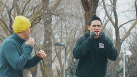 Boxninggenomkörare med instruktören utomhus Ung caucasian man i praktiserande skugga för svart hoodie som stansar i regnet _ stock video