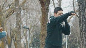 Boxninggenomkörare med instruktören utomhus Ung caucasian man i praktiserande skugga för svart hoodie som stansar i regnet _ arkivfilmer