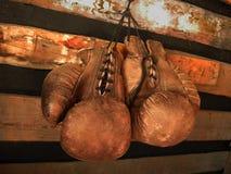 Boxninghandskar på väggen Gammalt tappningpar av lädertumvanten royaltyfri bild