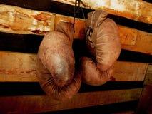 Boxninghandskar på väggen Gammalt tappningpar av lädertumvanten arkivbild