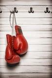 Boxninghandskar som hänger på träväggen Arkivbilder