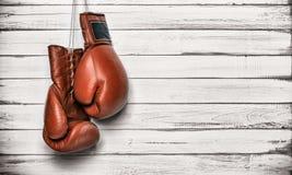 Boxninghandskar som hänger på träväggen Arkivfoton