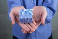 Boy& x27; рука s держа малую подарочную коробку с точками польки стоковые фото