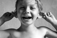 Boy. Pulls himself over the ears Royalty Free Stock Photography