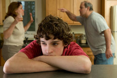 Boy (13-15) in pain as parents fight in background royalty free stock photos
