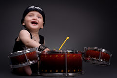 Boy. Dark portrait of  Beautiful boy playing the drums on a black background Stock Image