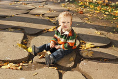 Boy. Hurt a little boy sitting on the path in the park Royalty Free Stock Photo