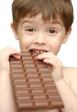 The boy. Bites a chocolate tile Royalty Free Stock Photography