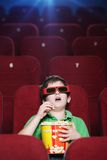 A boy at the 3D cinema. A boy with popcorn is watching a movie at the cinema royalty free stock photos