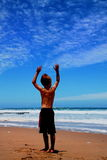 Boy. Standing on beach reaching to the sky Stock Photo