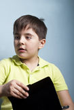 Boy with an absent gaze. Emotional portrait of a kid with an absent gaze, holding a tablet. Studio shot Royalty Free Stock Photography