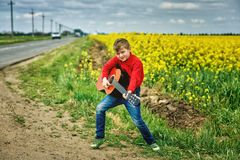 Boy with acoustic guitar outdoors. A boy with a guitar on the nature of the concept of children`s music education stock photography