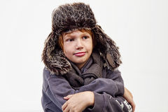 Boy Acting Funny in Fur Hat. Young boy acting funny while wearing huge fur hat with fur flaps Royalty Free Stock Photography