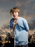Boy acting silly. Boy with fist raised smirking and acting silly on a sunset sky background Stock Image