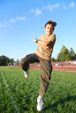 Boy in Action. Teenage boy jumping in a green grass covered sports field on a sunny day Royalty Free Stock Images