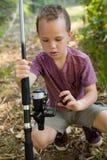Boy adjusting the fishing rod Stock Image