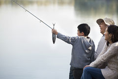 Boy admiring fishing catch with family at lake royalty free stock photo