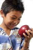 Boy admiring a red apple. Over white Royalty Free Stock Image