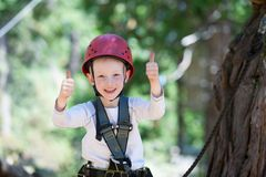 Boy at adventure park. Brave little boy having fun at adventure park and giving double thumbs-up Royalty Free Stock Photos