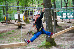 Boy in adventure park. Kid walking on logs in an adventure park Stock Photography