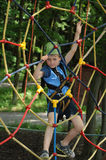 Boy in adventure park. Young boy climbing a rope way in an adventure park, lookingh to the camera Stock Photography