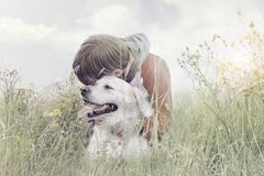 Boy affectionately hugs his dog in the middle of nature. Little boy affectionately hugs his dog in the middle of nature Stock Photo
