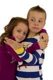 Boy afraid of a girl's hug wearing winter pajamas Royalty Free Stock Photo