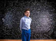Boy against big blackboard with mathematical symbols and formula. Boy in blue t-shirt against big blackboard with mathematical symbols and formulas Royalty Free Stock Image