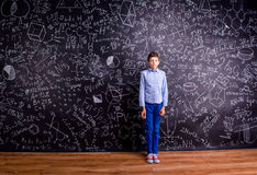 Boy against big blackboard with mathematical symbols and formula Stock Photos