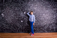 Boy against big blackboard with mathematical symbols and formula Royalty Free Stock Images