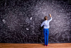 Boy against big blackboard with mathematical symbols and formula Royalty Free Stock Photography
