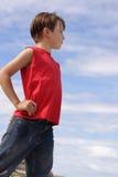 Boy against blue cloudy sky Royalty Free Stock Photos